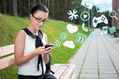 La colegiala o el estudiante hermosa que usa el teléfono elegante con differen Fotos de archivo libres de regalías