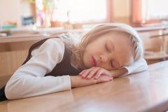 La colegiala que duerme en la escuela es sueño en el escritorio estudiante El estudiar del alumno foto de archivo libre de regalías