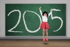 La colegiala salta en clase con el número 2015 Imagenes de archivo