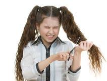 La colegiala scissors cortes su pelo Foto de archivo