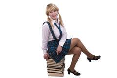 La colegiala se está sentando en la pila del libro. Fotografía de archivo libre de regalías