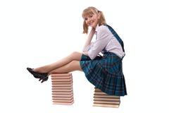 La colegiala se está sentando en la pila del libro. Imagen de archivo libre de regalías