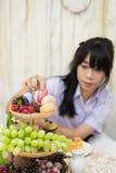 La colegiala tailandesa asiática en uniforme está escogiendo el macaron de la decoración de la bandeja de la comida fría del post imagenes de archivo