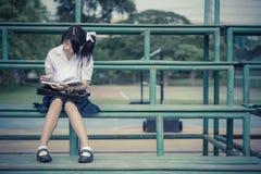La colegiala tailandesa linda es que se sienta y de lectura en un soporte en vintag Fotos de archivo