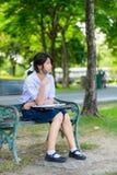 La colegiala tailandesa linda es que se sienta y que estudia en un banco Fotografía de archivo