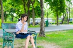 La colegiala tailandesa linda es que se sienta y que estudia en un banco Fotos de archivo
