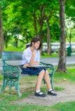 La colegiala tailandesa linda está estudiando y se imagina algo en un benc Fotos de archivo libres de regalías