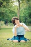 La colegiala tailandesa linda se está sentando en la hierba y está haciendo el sym del corazón Imagen de archivo libre de regalías