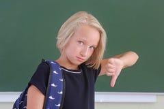 La colegiala triste con una mochila es el mostrar los pulgares abajo en una sala de clase cerca de la pizarra verde El niño no le Fotos de archivo