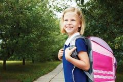 La colegiala va a la escuela con el bolso de escuela Fotografía de archivo libre de regalías