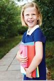 La colegiala va a la escuela con los libros de texto Foto de archivo libre de regalías