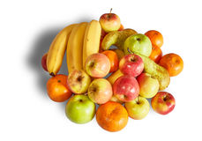 La colina de mandarinas, de manzanas y de plátanos maduros en el fondo blanco con la sombra Foto de archivo