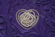 La collana della perla è sul tessuto coperto Fotografie Stock Libere da Diritti