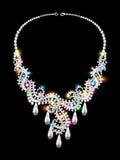La collana di una donna delle pietre preziose su fondo nero Immagine Stock
