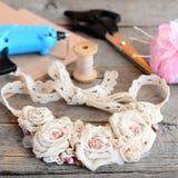 La collana floreale casuale del tessuto, incolla la pistola calda, le forbici, il filo, l'ago, feltro su una tavola di legno d'an immagini stock