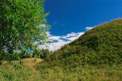 La collina in mezzo ai prati Fotografie Stock