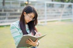 La colocación de las lentes del adolescente que lleva escribe un cuaderno en foo Imágenes de archivo libres de regalías