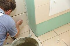 La colocación de las tejas en las paredes del cuarto de baño es muy un arte foto de archivo