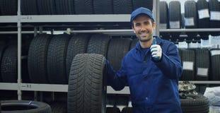 La colocación del neumático del especialista en el servicio del coche, los controles el neumático y el caucho pisan para la segur Foto de archivo libre de regalías