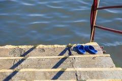 La colocación en el suelo de madera cerca del río es zapatos del verano: chancletas fotografía de archivo libre de regalías
