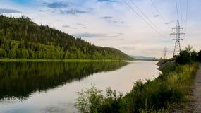 La colonna ad alta tensione del metallo sta sulle banche di grande fiume Le montagne e la foresta Immagini Stock