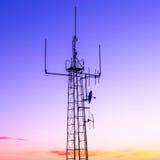La colonne avec l'émetteur radioélectrique contre le coucher du soleil colore le ciel Photographie stock