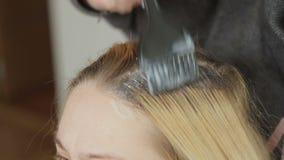 La coloración del cabello es blanca para una mujer hermosa en un salón de belleza Coloración de la raíz del pelo metrajes