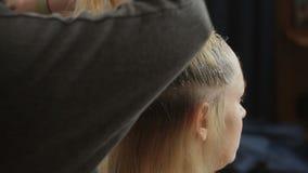La coloración del cabello es blanca para una mujer hermosa en un salón de belleza Coloración de la raíz del pelo almacen de video