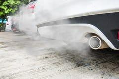 La combustión fumes saliendo del tubo de escape blanco del coche, concepto de la contaminación atmosférica Imagen de archivo