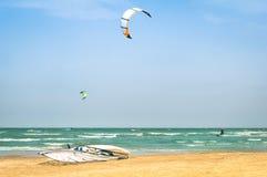 La cometa que practica surf en playa ventosa con windsurf tablero Fotografía de archivo libre de regalías