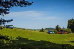 La comida campestre, coches parqueó en un claro en las montañas en el verde fotos de archivo