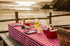 La comida campestre de la puesta del sol en el océano pasa por alto Foto de archivo libre de regalías