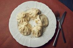 La comida china o asiática tradicional, bola de masa hervida cocida al vapor sirvió en la placa blanca con la bifurcación y el cu fotos de archivo libres de regalías