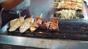 La comida de la calle en Asia, platos tradicionales de la carne y de los mariscos asó a la parrilla el fuego mercado de la noche  almacen de metraje de vídeo