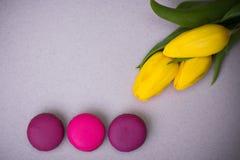 La comida de los macarrones con los tulipanes pica el fondo violeta para el día pascua de la mujer de la madre de las tarjetas de Imagen de archivo