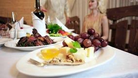 La comida deliciosa en la tabla en el restaurante, la carne, las uvas, el queso, la miel y el vino se sirven a los visitantes caf metrajes