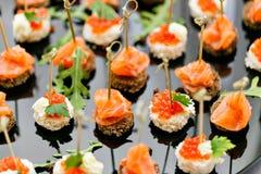 La comida fría en la recepción Surtido de canapes Servicio del banquete comida del abastecimiento, bocados con los salmones y cav Foto de archivo libre de regalías