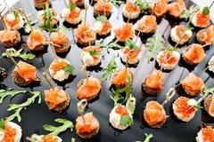 La comida fría en la recepción Surtido de canapes Servicio del banquete comida del abastecimiento, bocados con los salmones y cav Imagen de archivo libre de regalías