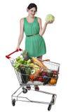 La comida llenada carretilla de las compras, mujer joven está sosteniendo una col Foto de archivo libre de regalías