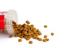 La comida para gatos seca se vierte de una taza de medici?n pl?stica para diversos tipos de gatos foto de archivo libre de regalías