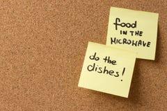 La comida pegajosa amarilla del post-it de la nota en la microonda, hace los platos imagenes de archivo