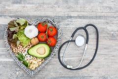 La comida sana en corazón y el colesterol adietan concepto en backgraund de madera con el estetoscopio fotografía de archivo libre de regalías