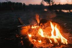 La comida se cocina en la hoguera en una cacerola, abre la tapa con la rama Gente en acampar en riverbank imagen de archivo libre de regalías