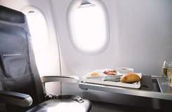 La comida sirvió a bordo del aeroplano de la clase de negocios en la tabla fotografía de archivo libre de regalías
