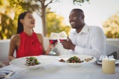 La comida sirvió en la placa mientras que los pares que tostaban sus copas de vino en el fondo Imagen de archivo libre de regalías