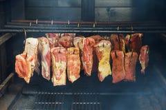 La comida tradicional fumó el jamón, tocino, cuello del cerdo en un ahumadero foto de archivo