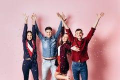 La compañía alegre de dos muchachas y dos individuos vestidos en ropa elegante están colocando y se están divirtiendo con confeti fotografía de archivo libre de regalías