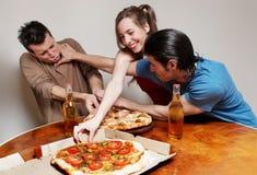 La compañía alegre de la juventud que come una pizza Fotos de archivo libres de regalías