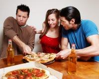 La compañía alegre de la juventud que come una pizza Imágenes de archivo libres de regalías
