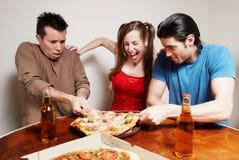 La compañía alegre de la juventud que come una pizza Fotos de archivo